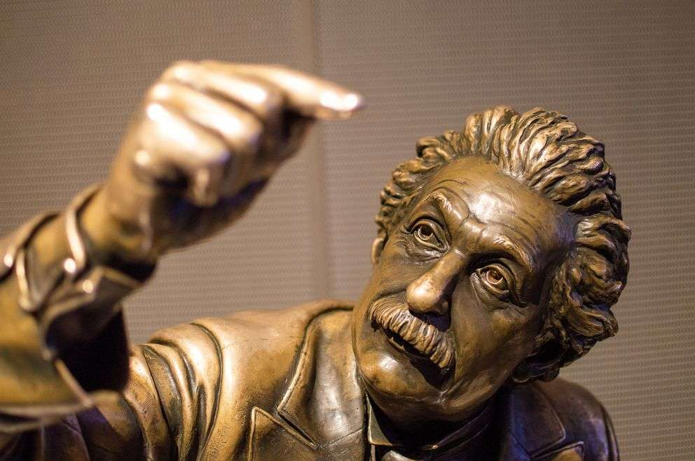 Albert Einstein sitting on a bench with his right finger held roughly a foot above his face